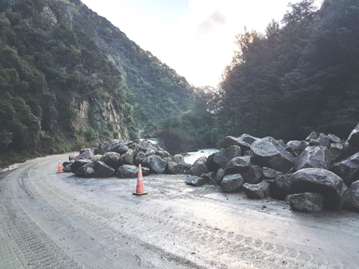 Large rock stockpiled on site where the road has been repaired, ready to be placed between the road and the stream as protection against future damage.